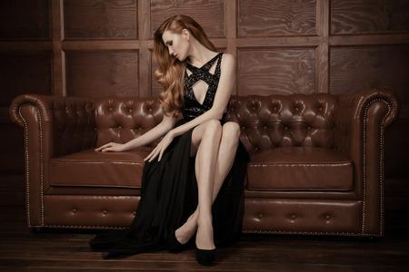 가죽 빈티지 소파에 앉아 아름 다운 고급스러운 여자의 이미지.