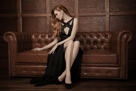 woman on couch: The image of a beautiful luxurious woman sitting on a leather vintage couch. Stock Photo