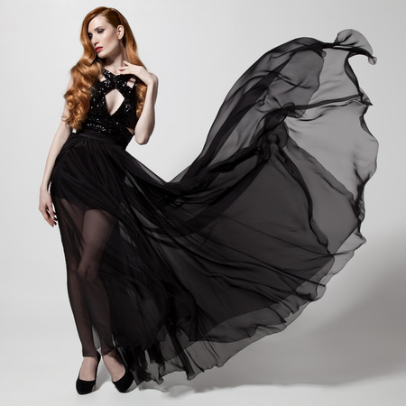 Fashion woman in fluttering black dress. White background. photo