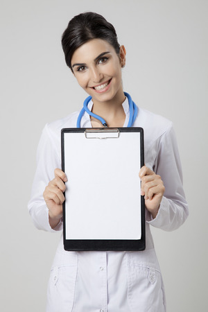Smiling medical doctor woman with empty blank in hands. photo