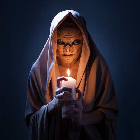 Warlock with candle in darkness. photo