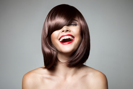 hair cut: Smiling Beautiful Woman With Brown Short Hair. Haircut. Hairstyle. Fringe. Professional Makeup. Stock Photo