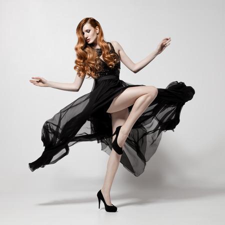 Mode vrouw in fladderende zwarte jurk. Witte achtergrond.