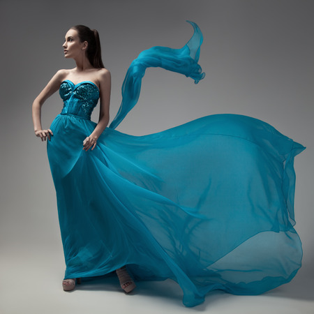Moda donna in abito blu svolazzanti. Sfondo grigio.