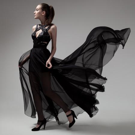Mode Frau in schwarzen Kleid flattert. Grauen Hintergrund.