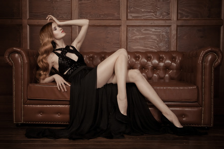 The image of a beautiful luxurious woman sitting on a leather vintage couch. Фото со стока