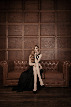 The image of a beautiful luxurious woman sitting on a leather vintage couch. photo