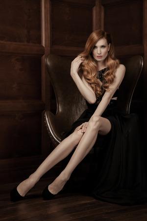 donne eleganti: L'immagine di una bella donna lussuosa seduta su una sedia d'epoca in pelle.
