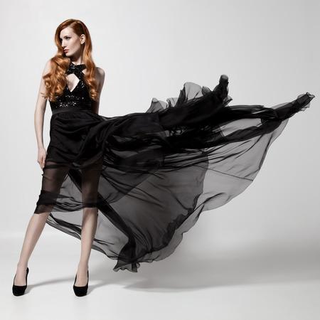 flyaway: Fashion woman in fluttering black dress. White background.