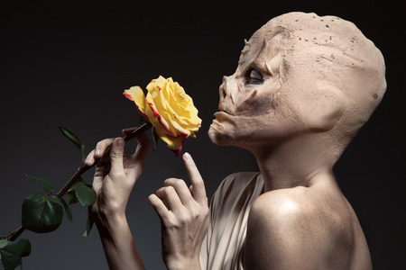 Beauty and the beast. Ugly witch with beautiful flower in hand. photo