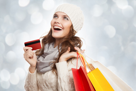 Shopping happy woman holding bags and credit card. Winter sales. photo