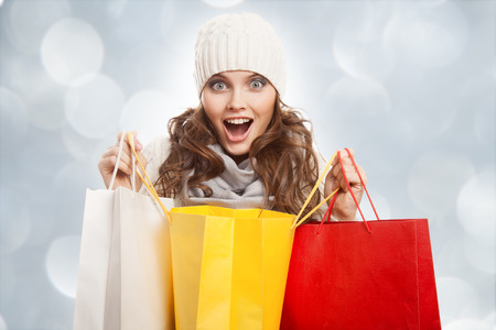 sales person: Shopping happy woman holding bags. Winter sales. Stock Photo