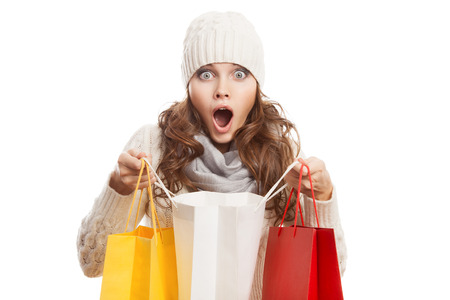 Shopping surprised woman holding bags. Winter sales.