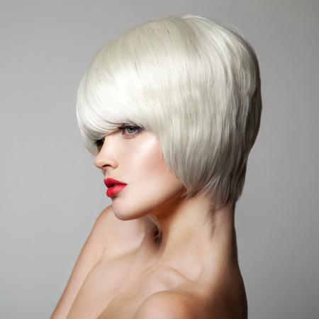 Fashion Beauty Portrait. White krátké vlasy. Sestřih. Účes. Fringe. Make-up. Vogue Style Woman. Šedé pozadí.