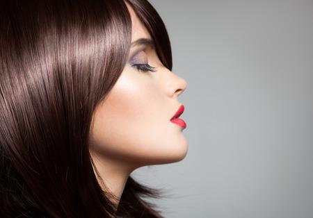 Modelo de la belleza con el pelo largo de color marrón brillante perfecto. Retrato de primer plano.