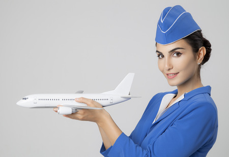 Charming Stewardess Holding Airplane In Hand. photo