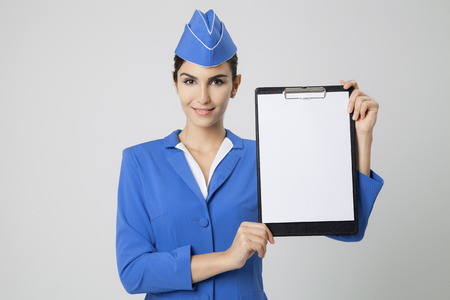 an attendant: Charming Stewardess Dressed In Blue Uniform with empty blank in hands.