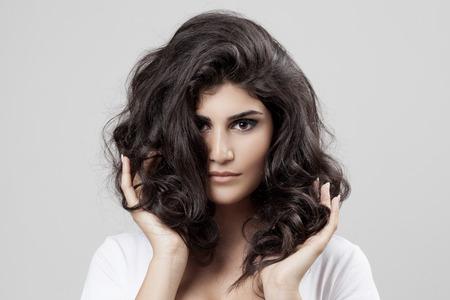 Mooie brunette vrouw. Krullend lang haar. Stockfoto
