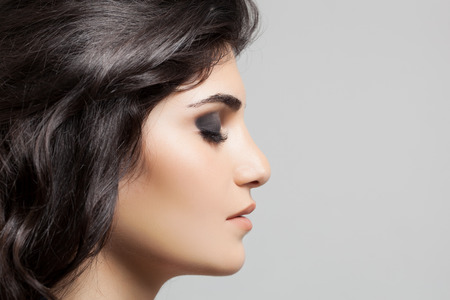 sideview: Beautiful Brunette Woman. Hairstyle and Make-up. Stock Photo