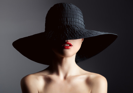 labios rojos: Mujer hermosa en el sombrero. La moda retro. Fondo Oscuro.