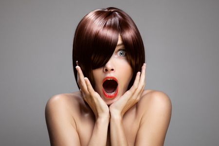 Surprised woman with perfect long glossy brown hair. Close-up portrait. photo
