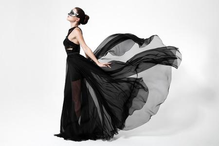 ファッション女性黒いドレスを舞います。白い背景。