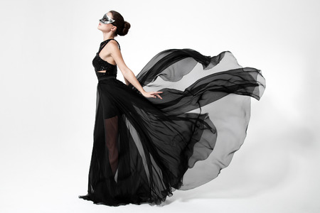 Mode vrouw in fladderende zwarte jurk. Witte achtergrond. Stockfoto