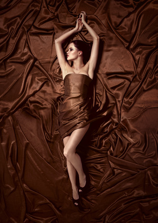 Beautiful woman lying on a chocolate fabric. photo