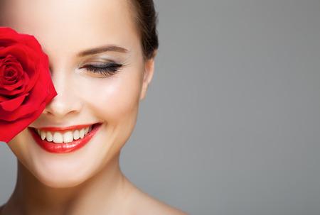 赤いバラで笑顔美人のクローズ アップの肖像画。メイク顔。