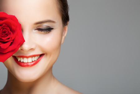Close-up portrait of beautiful smiling woman with red rose. Make-up face. Stockfoto