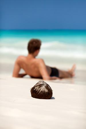 33083919-man-lying-on-a-beach-on-a-desert-tropical-island-focus-on-coconut-.jpg?ver=6