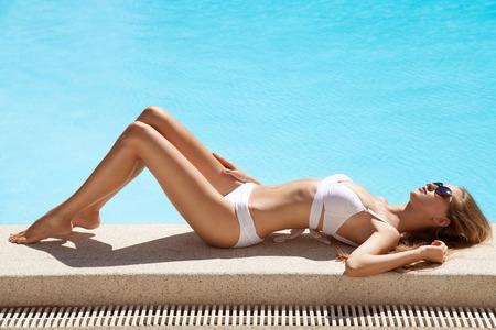 swimsuit: Young woman sunbathing near swimming pool.