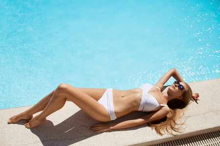 Young woman sunbathing near swimming pool.