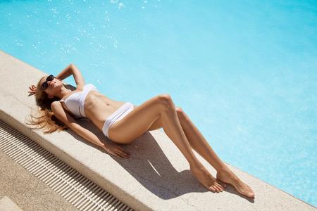 Young woman sunbathing near swimming pool. photo