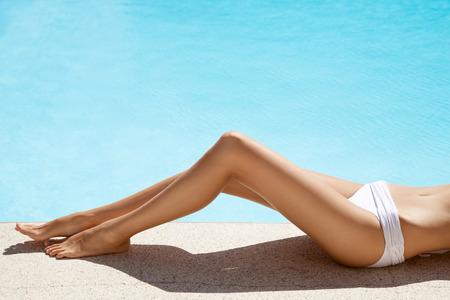 Mooie vrouw benen. Zonnen in de buurt van het zwembad.