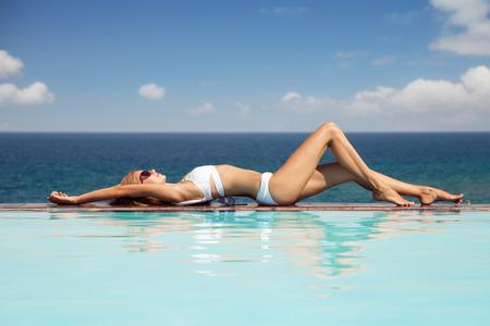 젊은 아름 다운 여자 일광욕. 수영장에서 멋진 바다 전망.