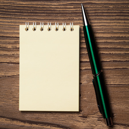 Pen and notebook on wooden table. photo