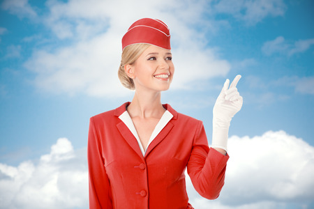 Charming Stewardess Dressed In Red Uniform Pointing The Finger. Sky With Clouds Background.