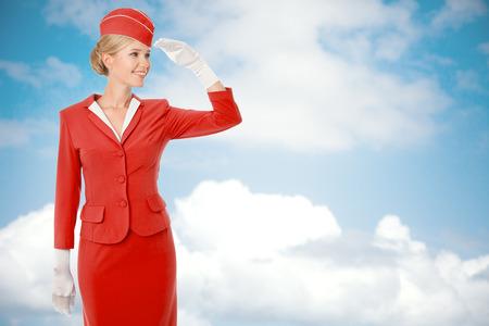 air hostess: Hôtesse de charme en uniforme rouge. Ciel avec des nuages ??de fond.