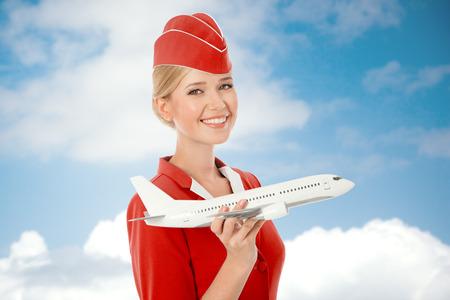 Charming Hostess azienda aereo in mano. Cielo con nuvole di sfondo. Archivio Fotografico - 33418609