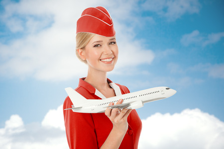 Charming Stewardess Holding Airplane In Hand. Sky With Clouds Background. photo