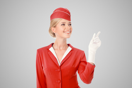 Charming Stewardess Dressed In Red Uniform Pointing The Finger On Gray Background. Stock Photo