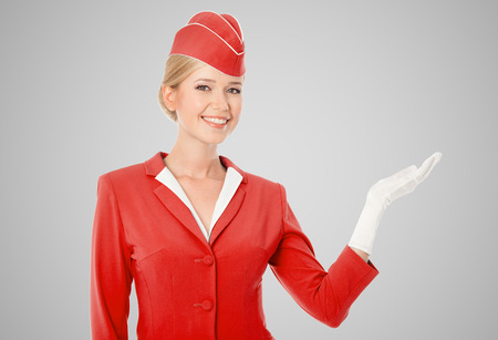 flight crew: Charming Stewardess Dressed In Red Uniform Holding In Hand On Gray Background.
