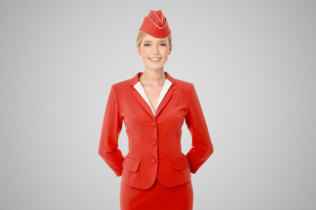 an attendant: Charming Stewardess Dressed In Red Uniform On Gray Background.
