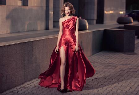 Giovane bella donna in vestito d'ondeggiamento rosso. Sfondo della città. Archivio Fotografico - 34745953