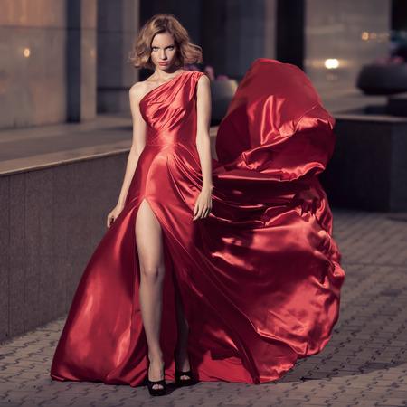 poses de modelos: Mujer hermosa joven en vestido rojo que agita. Fondo de la ciudad.