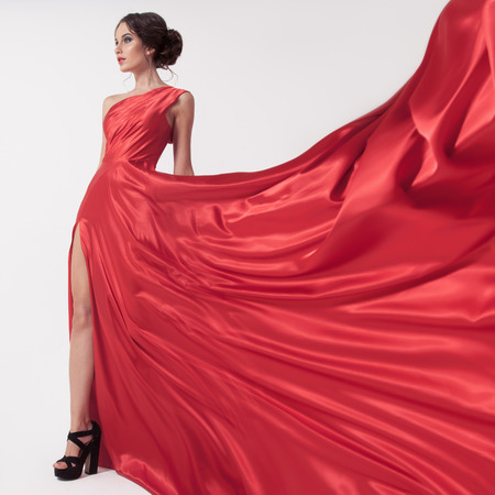 fluttering: Young beauty woman in fluttering red dress. White background.