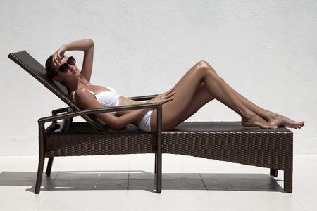 Beautiful tan female model sunbathing in bikini on chaise-longue. Against white wall. photo