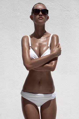 Beautiful tan female model posing in bikini and sunglasses. Against white wall. photo