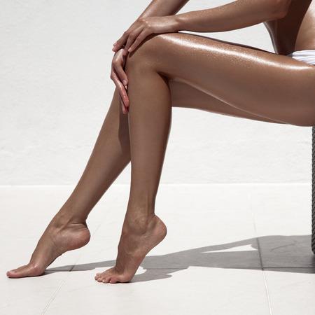 Beautiful woman tan legs. Against white wall. photo